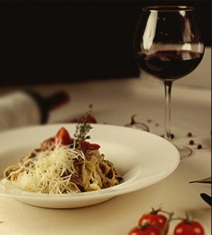 Foto de um cálice de vinho e um prato com macarrão servido